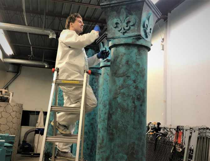 Artist painting Styrofoam pillars